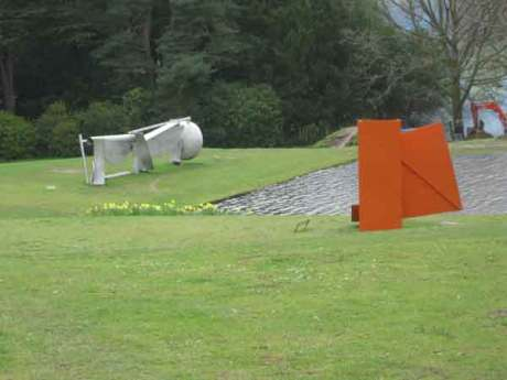 Sir Anthony Caro british sculptor at Chatsworth House in Derbyshire, metal painted sculpture,orange steel plates in grass,
