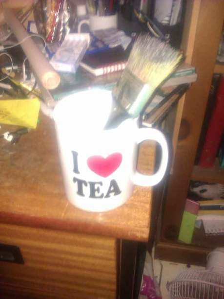 the artist's studio belonging to the artist Gregory, a photograph of Gregory's tea mug with his paint brush stuck in it, I love tea is printed on the artist's tea mug on his desk,